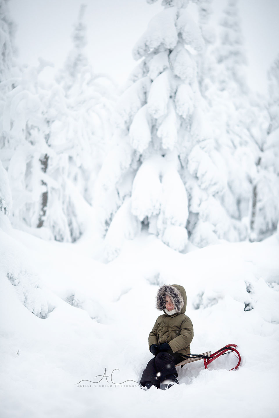 London Children Winter Photo Session | 5 year old boy smiles while sitting on a sledge in snowy mountains