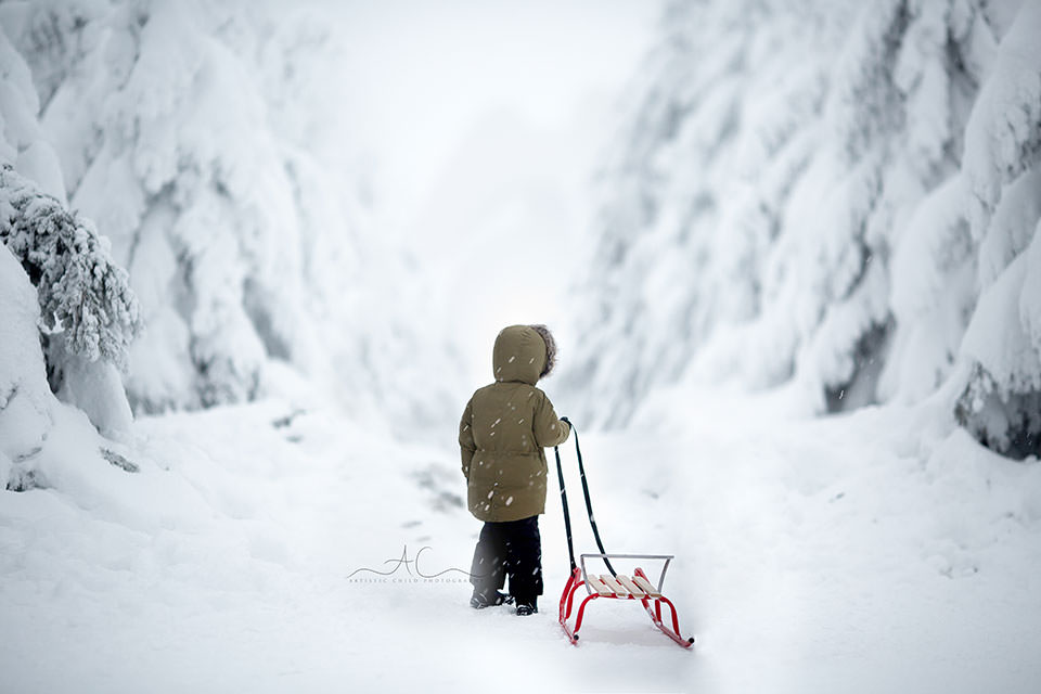 London Children Winter Photo Session | photo of a boy walking with his sledge into snowy mountains