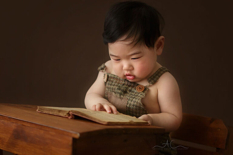 South East London Baby Boy Photographer | a close up portait of a baby boy reading a book