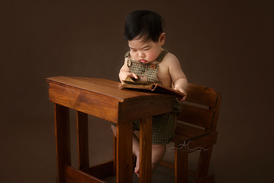 portrait of a baby boy reading a book at the old fashioned children wooden desk   South East London professional photo session