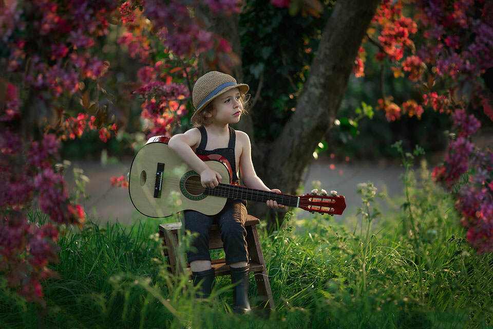 spring photo of a 4 year old boy playing his guitar under blossom tree | London