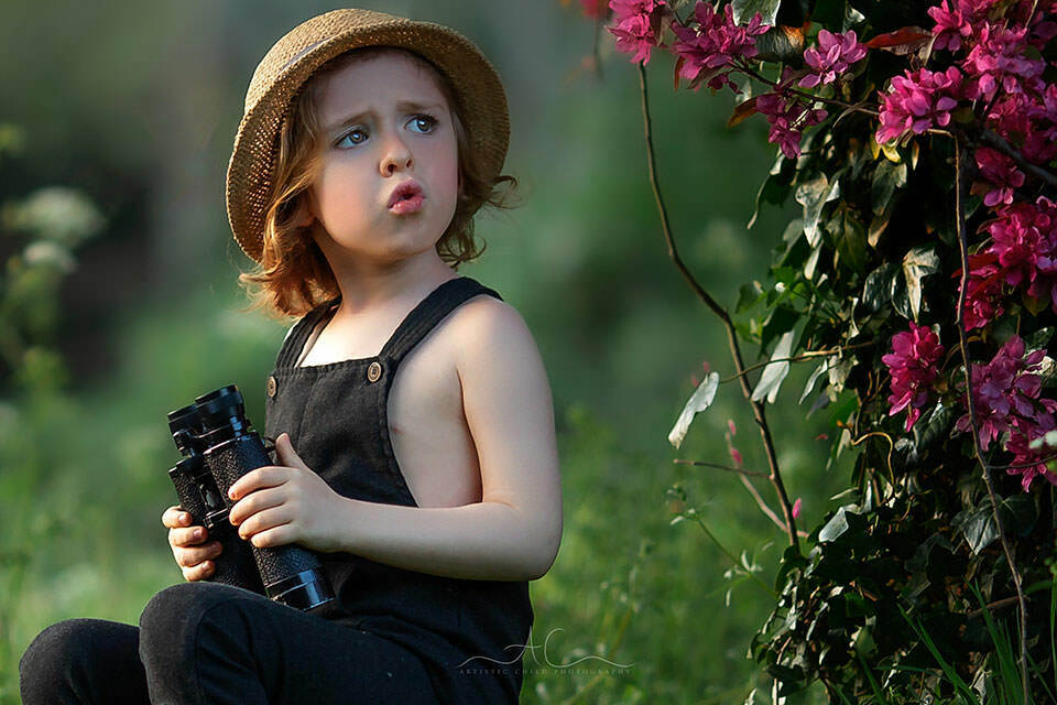 a close up portrait of a 4 year old boy with binoculars sitting under blossom tree | London