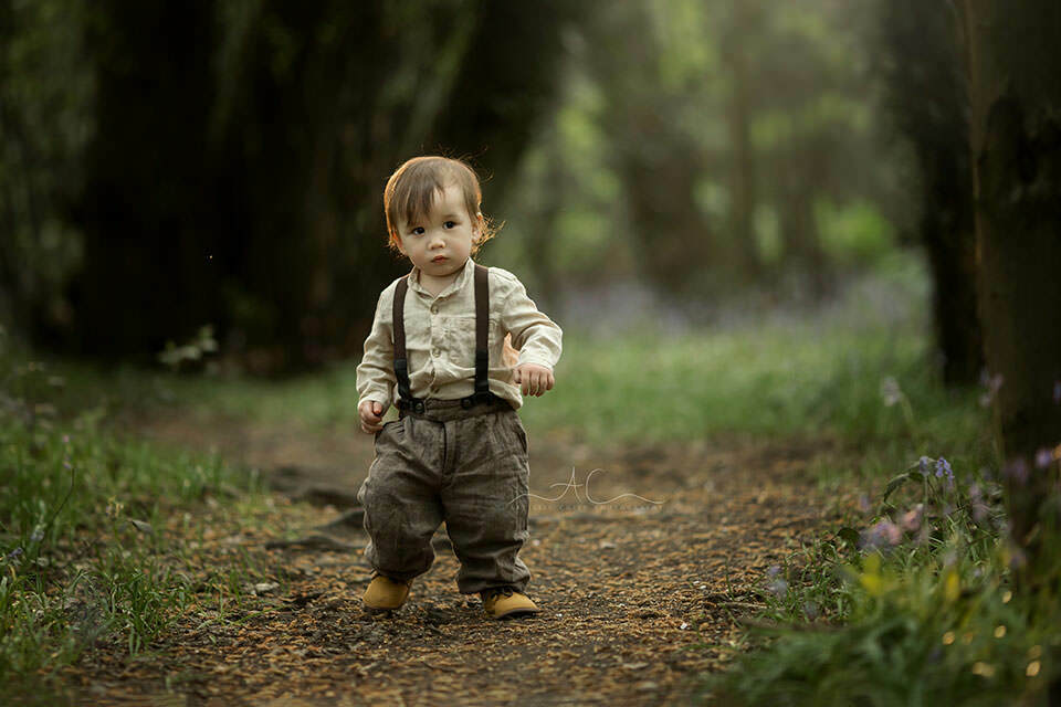 backlit photo of a 1 year old boy walking in woods during spring season | London
