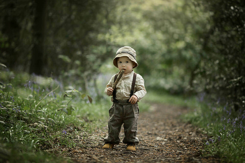 1 year old boy plays with a stick in woods during a professional photo session | London