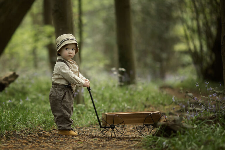 Spring London Toddler Photo Session | 1 year old boy playing with wooden trolley in woods