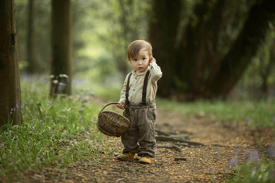 Spring London Toddler Photo Session | 1 year old boy walks in woodland park with a wicker basket in his hand