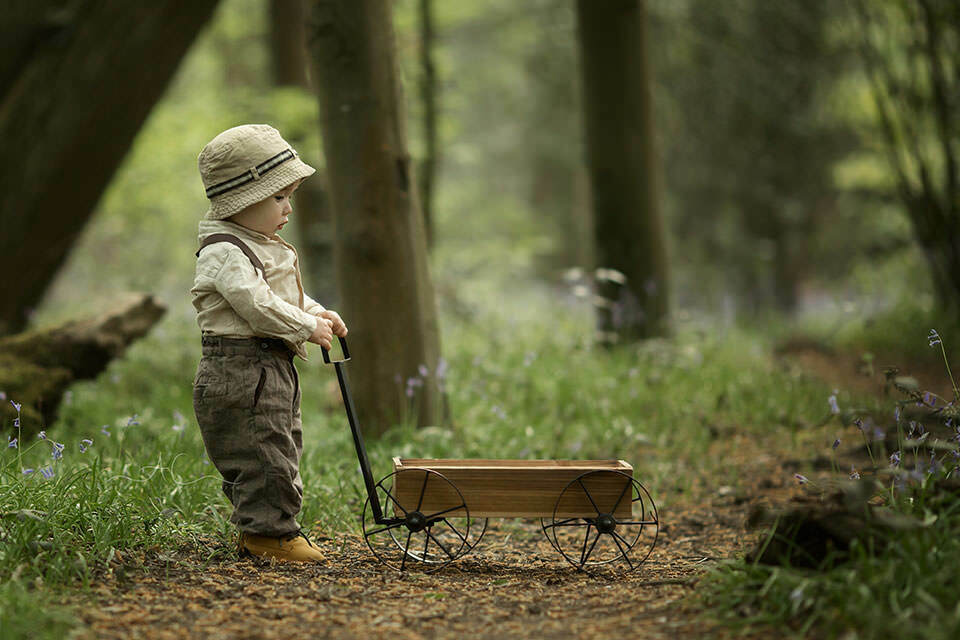 Spring London Toddler Photo Session | 1 year old boy pulls wooden trolley in woods