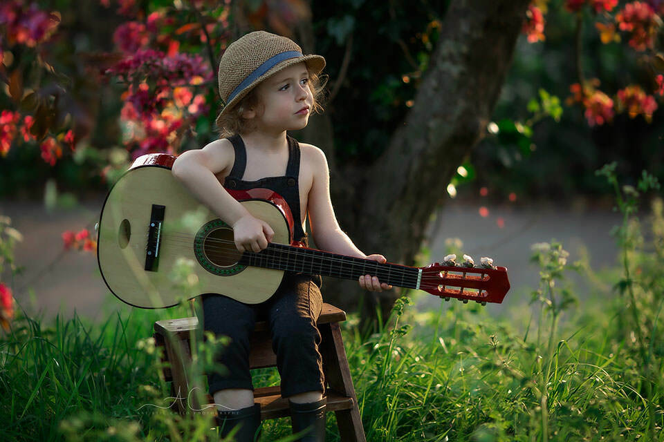 Top London Child Spring Photography |  4 year old boy plays the guitar under the blossom tree