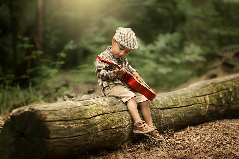 portrait of a toddler boy wearing a flat cap and playing the guitar on the log in the park | London