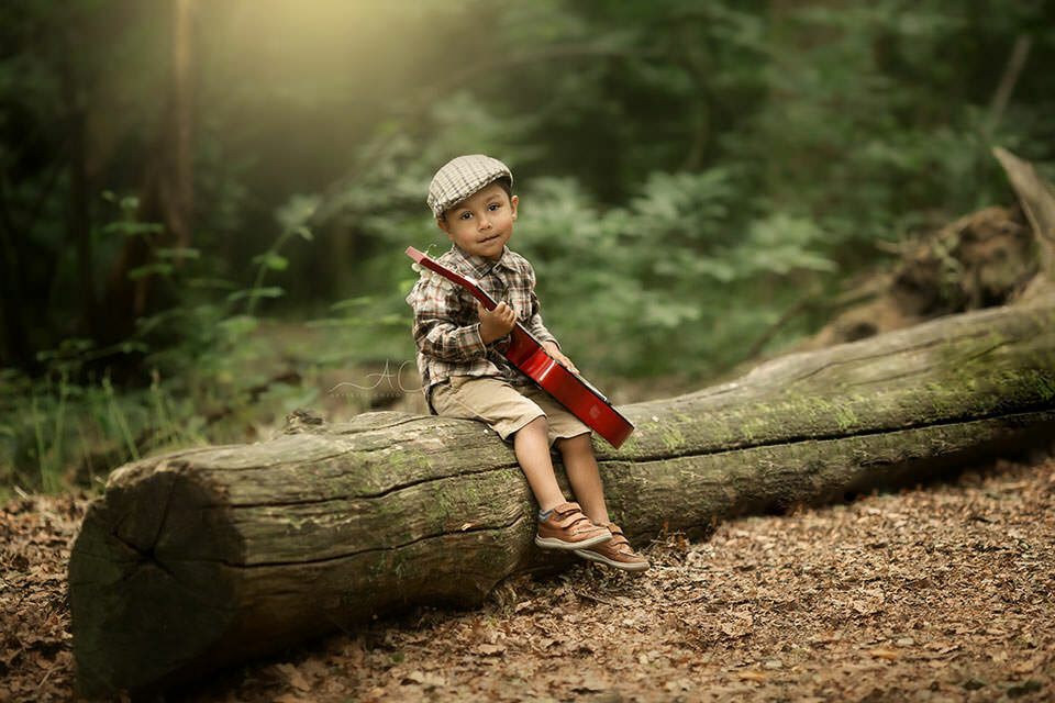 toddler boy plays a guitar on a log in the park | London