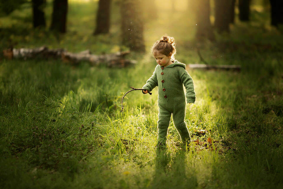 3 years old boy runs in woods with a stick in his hand during spring photo session   London
