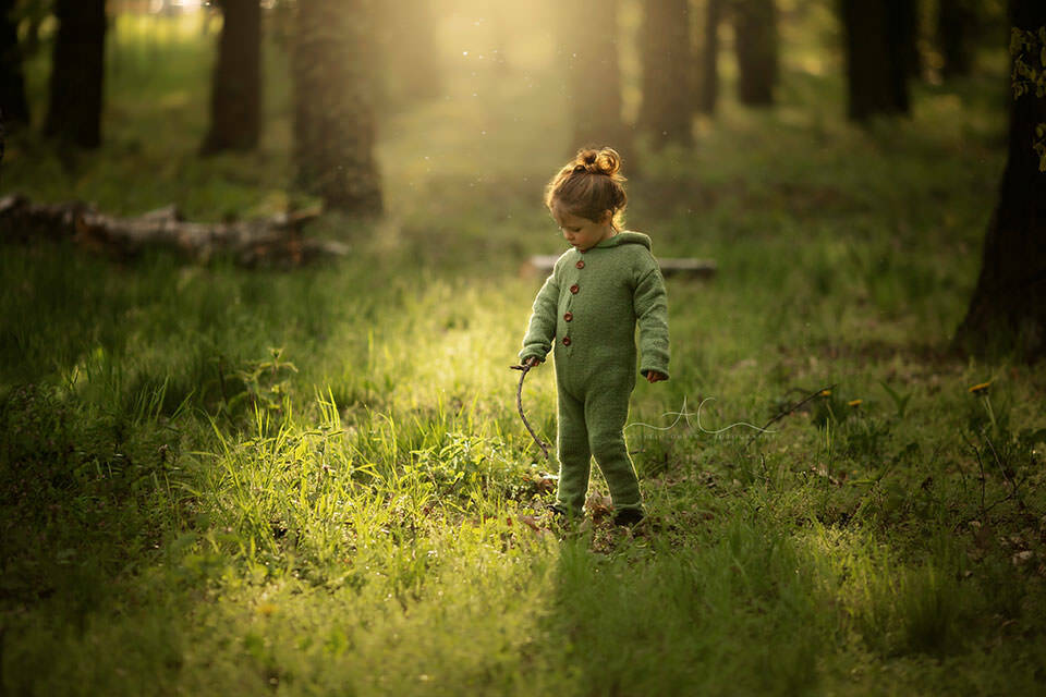 backlit sunshire image of a 3 year old boy playing in woods with his wooden stick   London