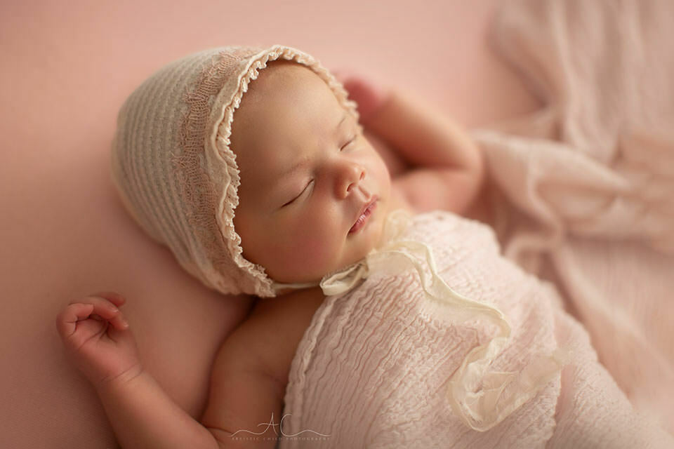 backlit portrait of a newborn baby girl in a pink bonnet | South East London