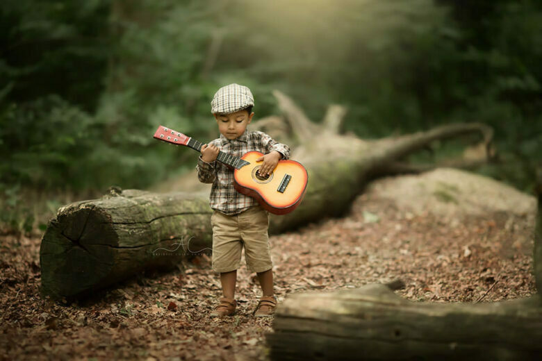Beautiful London Toddler Images   portrait of a toddler boy playing a guitar in the park