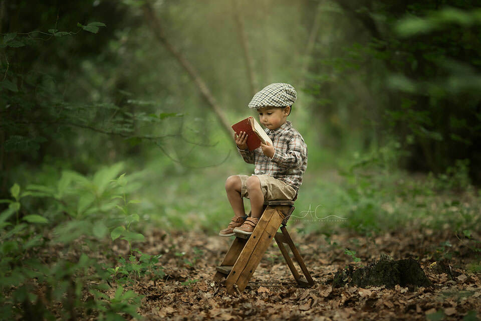 Beautiful London Toddler Images | toddler boy reads a book while sitting on a wooden steps in the park
