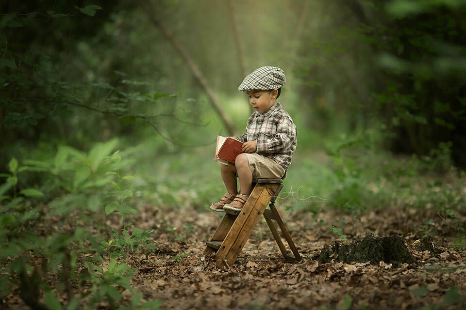 Beautiful London Toddler Images | photo of a toddler boy opening a book in the park