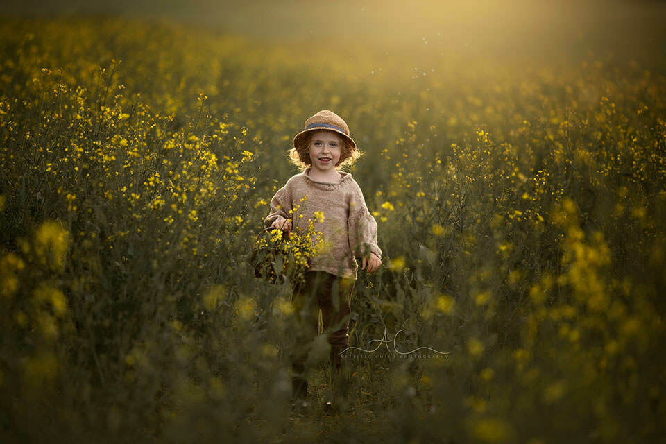 Rapeseed Field South East London Child Photography | smily 4 year old boy carries a wicker basket in rapeseed field