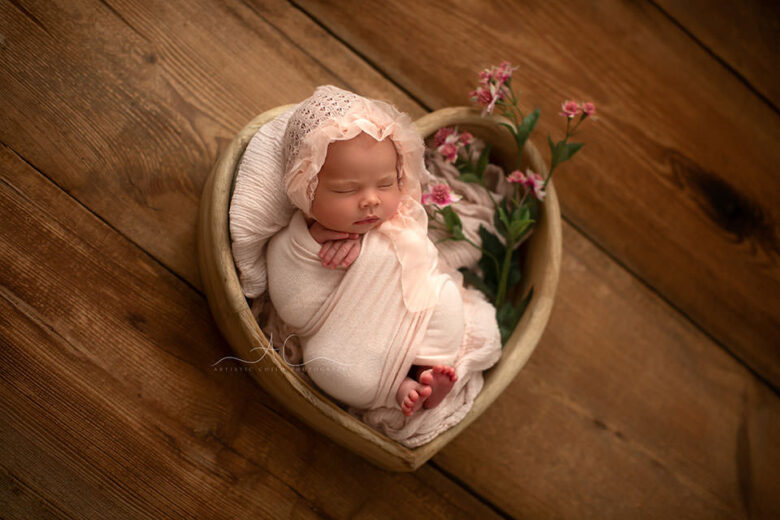 photo of a newborn baby girl pictured in a wooden heart bowl with flowers | Bromley