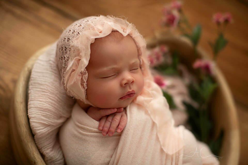 a close up portrait of a newborn baby girl wearing a beautiful hand made pink bonnet | Bromley