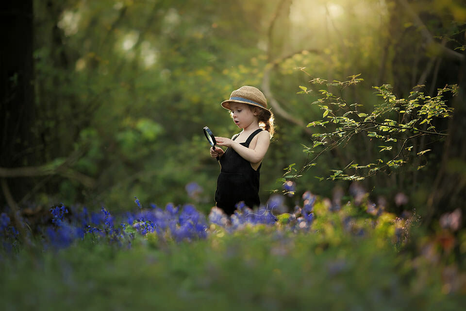 Bluebells London Boy Photo Session | 4 year old boy plays with magnifying glass while observing bluebells flowers