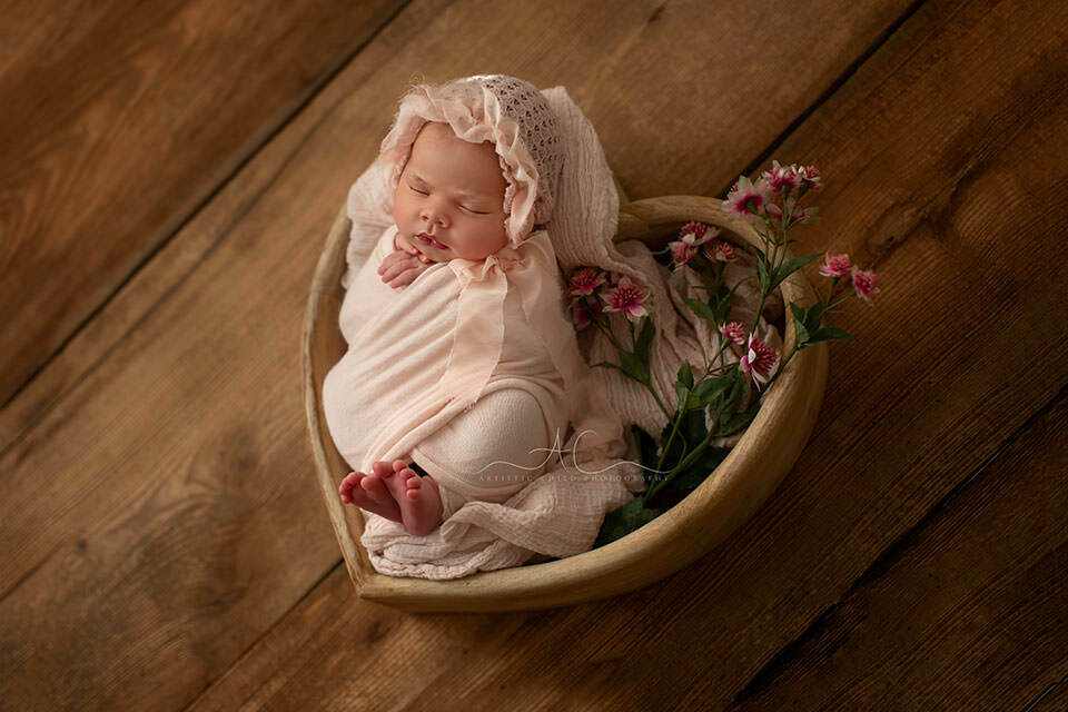 Bromley Newborn Baby Girl Photo Session | backlit portrait of a newborn baby girl sleeping in a heart bowl