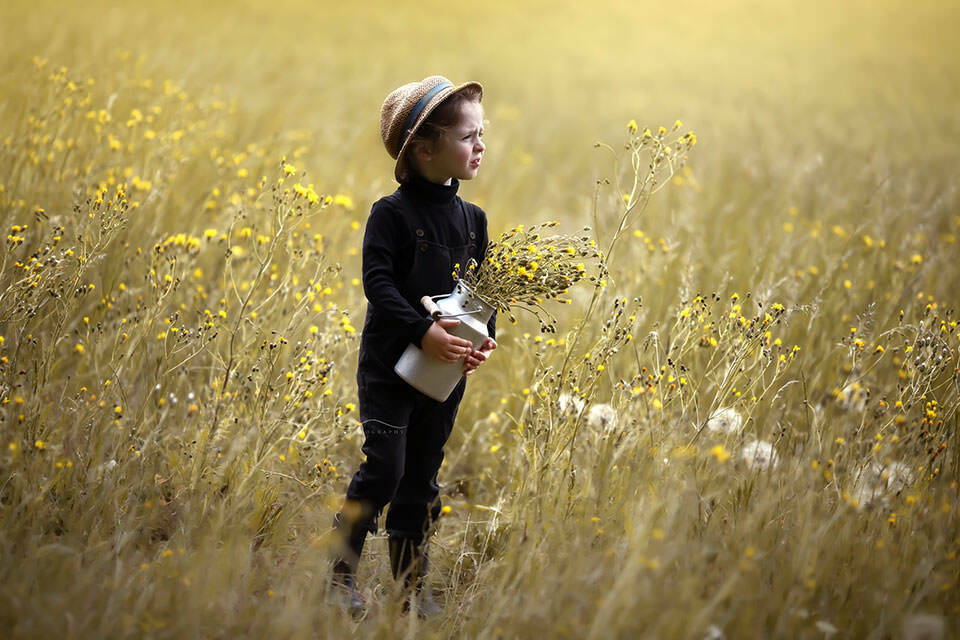 Summertime London Children Photo Session | 4 year old boy holding a bunch of wild flowers in the middle of a field