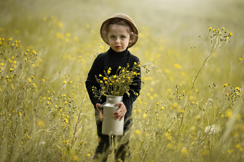 summer portrait of a 4 year old boy picking the wild flowers | London