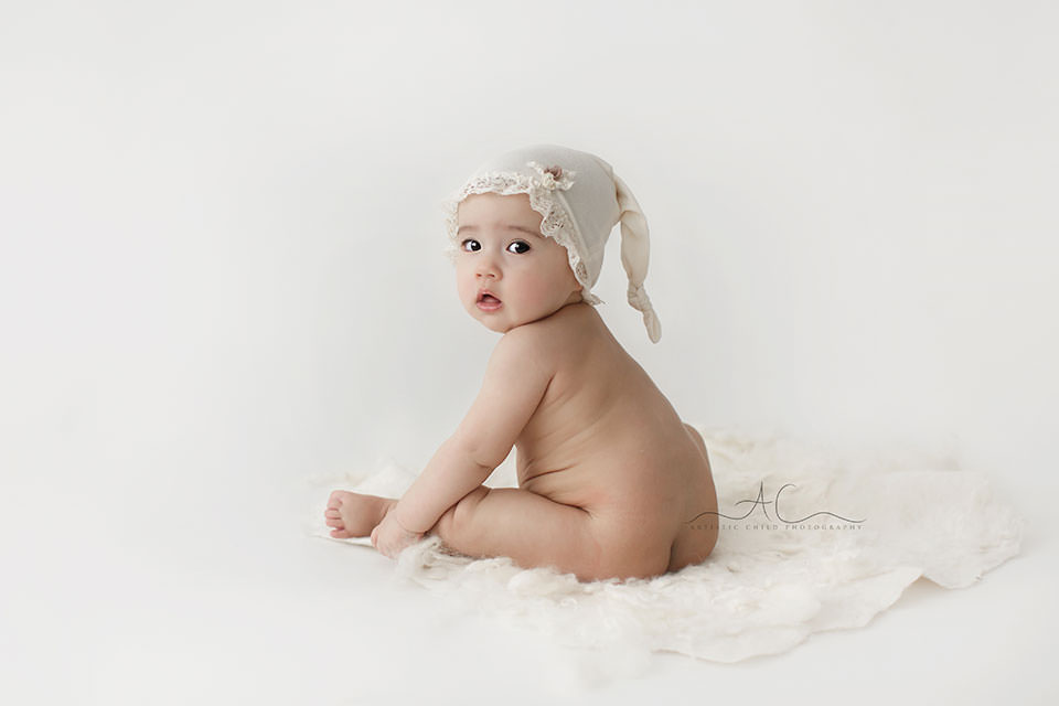 top portrait of a 7 months old baby girl wearing a lacey sleepy hat  South East London