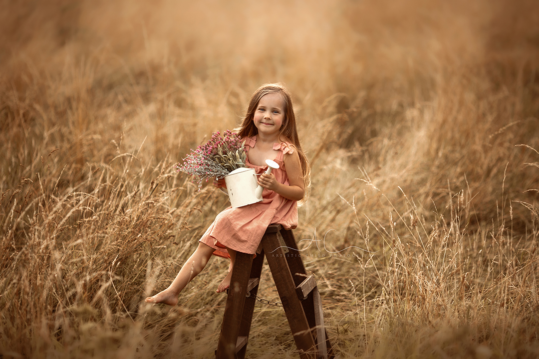 South East London   portrait of a 5 year old girl sitting on wooden ladder steps in a field of long grass