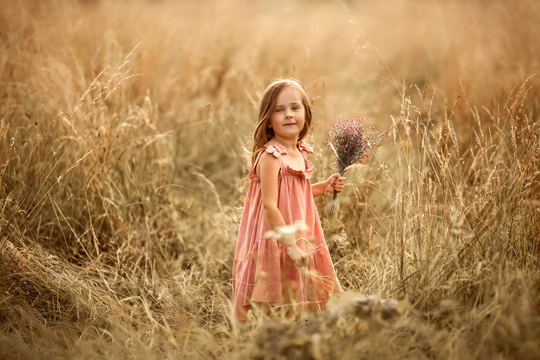portrait of a girl holding a bunch of flowers in a long grass field