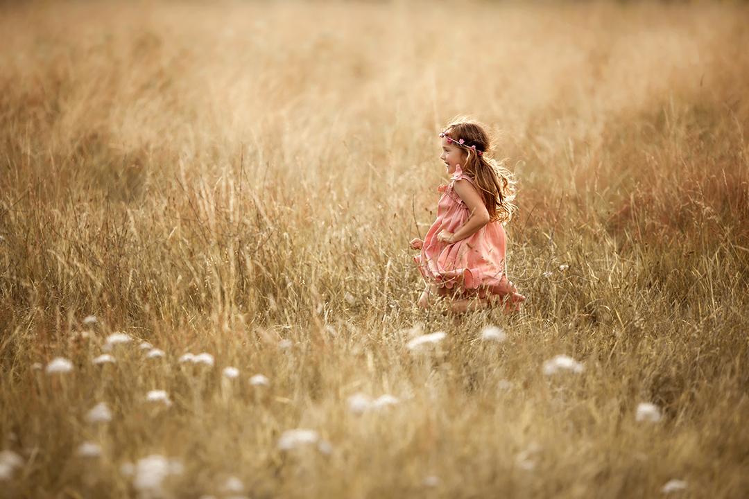 South East London Kids Photos   5 year old girl runs through a field of long grass