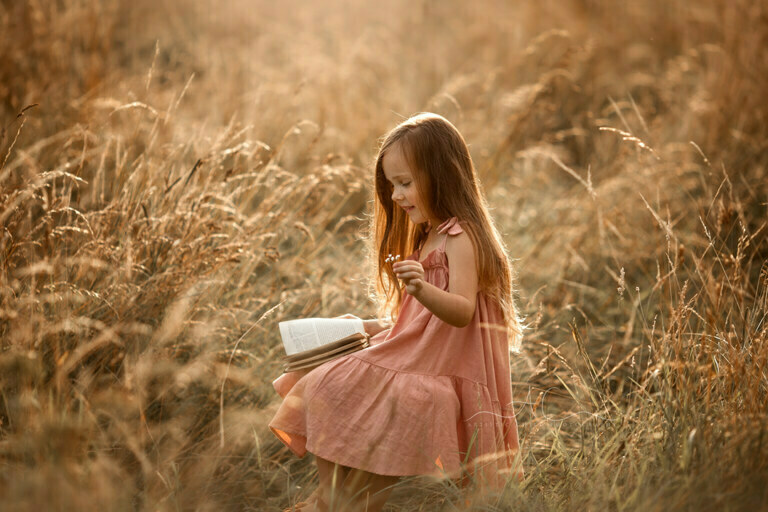 South East London Kids Photos | beautifully backlit portrait of a 5 year old girl reading a book in the middle of a long grass field