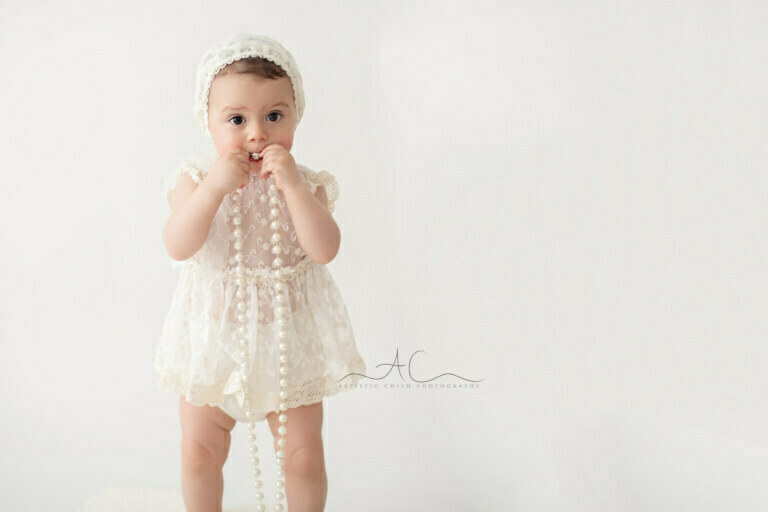 Professional South East London Toddler Photo Session   portrait of a 16 months old girl standing with pearls in her hands